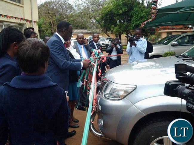 Eastern Province Permanent Secretary Chanda Kasolo being assisted by Chadiza District Commissioner George Phiri cutting the ribbon to signify the official handover of the nine vehicles to District Commissioners in Eastern Province in Chipata