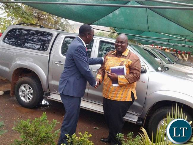 Eastern Province Permanent Secretary Chanda Kasolo congratulating Chipata District Commissioner Kalunga Zulu after handover ceremony of the newly procured vehicles for the District Commissioners in Eastern Province in Chipata