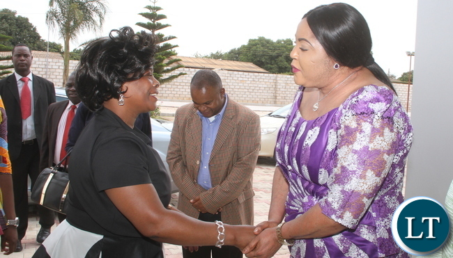 First Lady Esther Lungu being embraced by Defence minister Siamunene's wife Purity on arrival at ZAF Chamber Valley Officers' Mess for the First Lady Fundraising Ladies' luncheon to raise funds for the construction of the Air Headquarters Hospital at City Airport in Lusaka on Saturday , October 31,2015 -Picture by THOMAS NSAMA