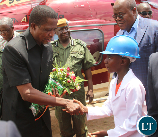 President Edgar Lungu receiving flower from a Chikonkomene Grade 4 pupil Lameck Goma.