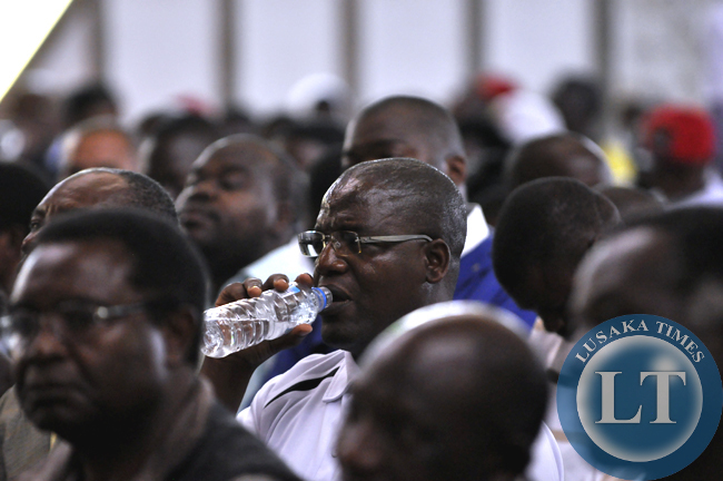 Law Association of Zambia vice president George Chisanga cools off with a bottle of mineral water after delivering a speech on behalf of his organisation