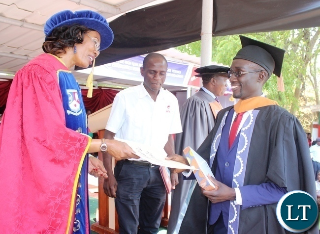 Mulungushi University Vice Chancellor Prof. Hellicy Ng'ambi presenting the ZANACO prize for the best graduating student in Bachelor of commerce accounting and finance stream to Wamulume Mushala during Mulungushi University 7th graduation ceremony
