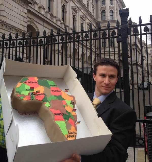 One of the campaigners outside Downing Street – where the UK Prime Minister and Chancellor live – holds up a cake of Africa with New Alliance countries marked out with flags. Photo: WDM