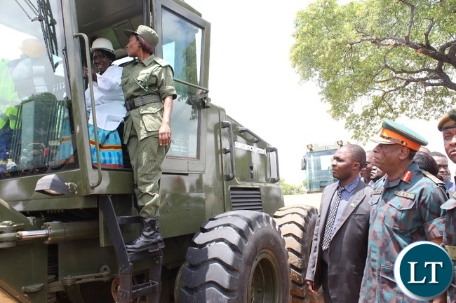 Acting President Inonge Wina operating a grader for Zambia National Service (ZNS) as ZNS Commandant Lt. Gen. Nathan Mulenga (r) looks on during the launch of Countrywide Feeder Roads Rehabilitation exercise worth K16.2 billion in Litoya area of Nalolo District in Western