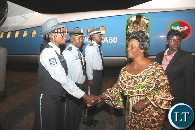 irst Lady Esther Lungu  greets flight crew member Brenda Phiri on arrival at City Airport from Mongu District where she handover of assistive devices to the victims of Konzo diseases in Luatembo village  on Tuesday, December 15,2015 -Pictures by THOMAS NSAMA