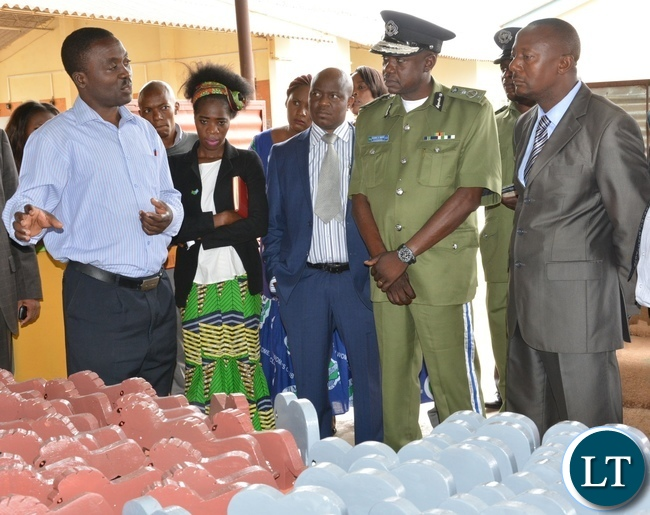 The head of department of construction at Lusaka Youth Center Mr. Kaimana Charles shows part of the work to the Acting Permanent Secretary Ministry of Youth Sport and child Development Mr. Alfonso Banda (r) next the deputy inspector general of police Mr. Engine Sibote (c) during the graduation ceremony for the Lusaka youth resource center