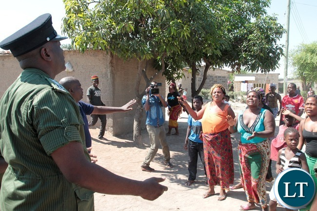 Resident probes with the Inspector General of Police Kakoma Kanganja who was inspecting Mtendere Police Post in Chawama Compound Kafue that was damaged by people in the area