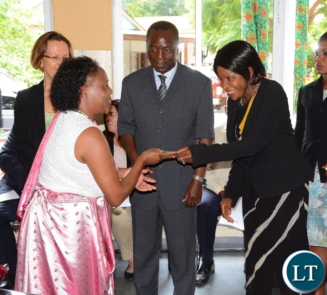 Ministry of Home Affairs Permanent Secretary Elwyn Chomba gives Alexia Nyiraminani resident permit whilst her Deputy Permanent Secretary Willies Manjimela (c) looks on during the launch of Integration for Former Rwandan Refugees at the Commissioner for Refugees Conference room