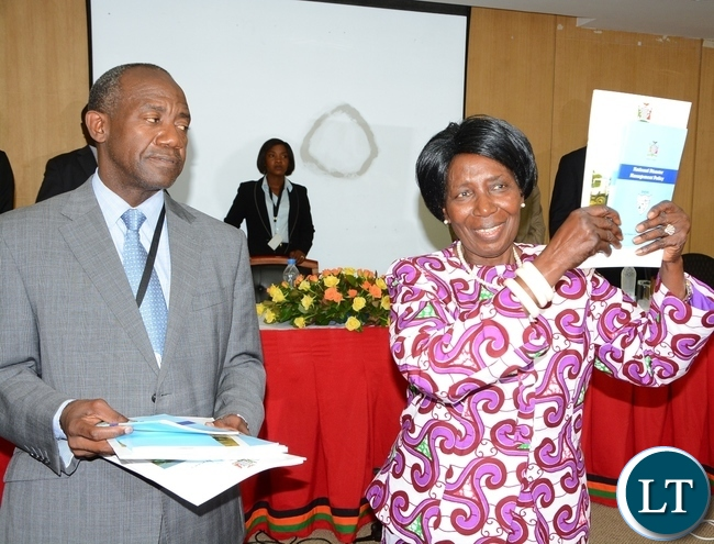 Vice President Inonge Wina shows the newly launched Disaster Management Policy and Settlement whilst DMMU Coordinator Patrick Kangwa looks on
