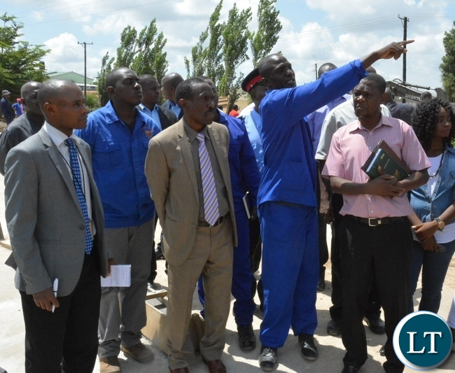 Chunga bridge project Superviser Martin Sibalwa shows Deputy Minister in the office of the Vice President Lawrance Sichalwe where water comes from during the tour of the Chunga bridge in Matero