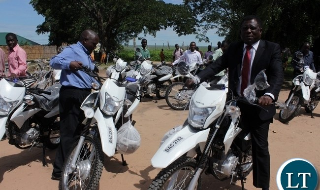Mongu District Commissioner Susiku Kamona (r) on a motorbike during the donation of 14 motorbikes and 300 bicycles to Government Ministries involved in Scaling Up Nutrition (SUN) activities to fight against malnutrition in children in Mongu