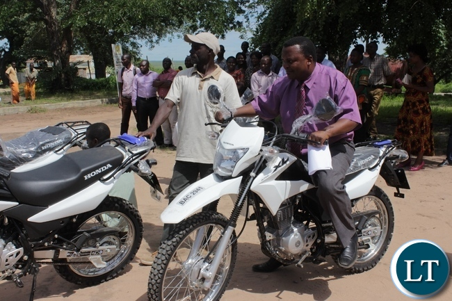 Mongu District Agriculture Officer Chabalanga Ng'ambi (r) on a motorbike during the donation of 14 motorbikes and 300 bicycles to Government Ministries involved in Scaling Up Nutrition activities to fight against malnutrition in children in Mongu