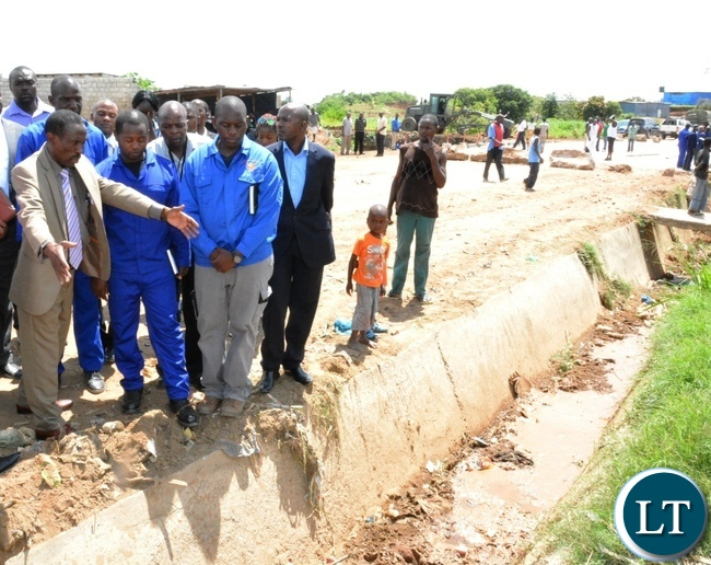 Deputy Minister in the office of the Vice President Lawrance Sichalwe (left) inspects drainage during the tour of the Chunga bridge in Matero