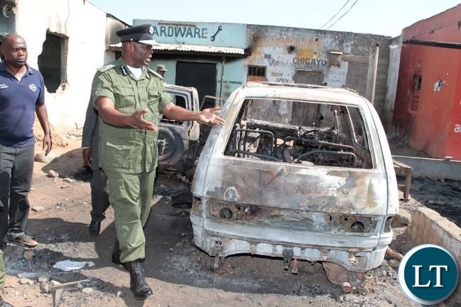 Inspector General of Police Kakoma Kanganja inspects cars that were burnt at Lumumba Police Post in Chawama Compound Kafue