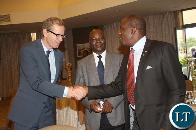 Swedish Ambassador to Zamba Henerik Cederin shaking hands with Stanbic Bank - Zambia Charles Mudiwa