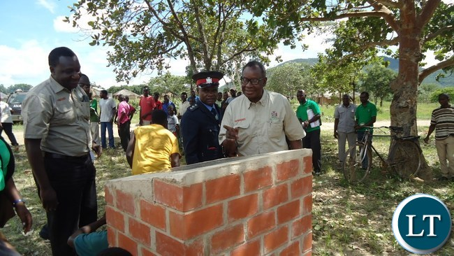 Health Minister Dr Joseph Kasonde checking a plague before launching Katambo health post in Chipata , while looking on is Eastern Province Medical Officer Dr Abel Kabalo