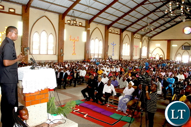 President Lungu flanked  by St Regina Parish Priest Fr Mwape during Mass at Regina Catholic Church in Lusaka's Chawama constituency on Sunday, January 3,2015 -Picture by THOMAS NSAMA