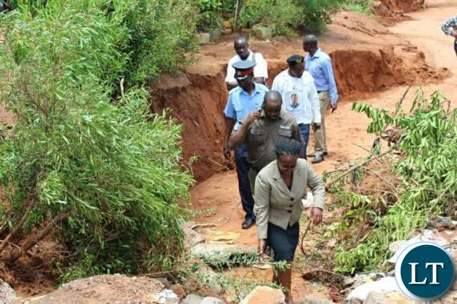 Livingstone Town Clerk Vivian Chikoti (in front) and Livingstone District Commissioner Omar Munsanje (behind) inspects some roads that have been damaged in Mwandi Extension following heavy rains experienced in Livingstone