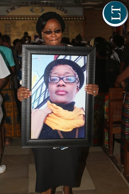 A Faith Kandaba friend displaying her portrait at the end of the Requiem mass celebrated at St Francis of Sales Parish, Lusaka at Thornpark Township.