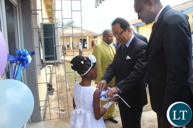 Japanese Ambassador to Zambia Mr. Kiyoshi Koinuma(Right) being welcomed by a flower girl to cut the ribbon to signify the official opening of the new rehabilitated X-Ray which houses the digital X-Ray machine handed over to Monze Mission Hospital by the Japanese Government