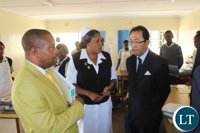 A Female Nurse(Centre in white uniform) explains to Japanese Ambassador to Zambia Mr. Kiyoshi Koinuma (right)the operations and services offered by the of the Hospital as Hospital Acting Medical Superintendent Dr Kakanda Ngalukela (left) follows the conversation.