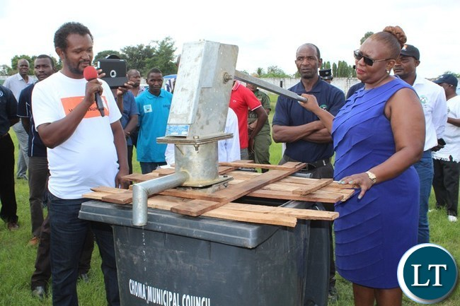 ENERGY and Water Development Minister Dora Siliya pumps water using borehole during the National water day celebration at Choma stadium yesterday. On the left is World Vision Hydro geologist Exenos Chimfwembe explaining how the water borehole works.