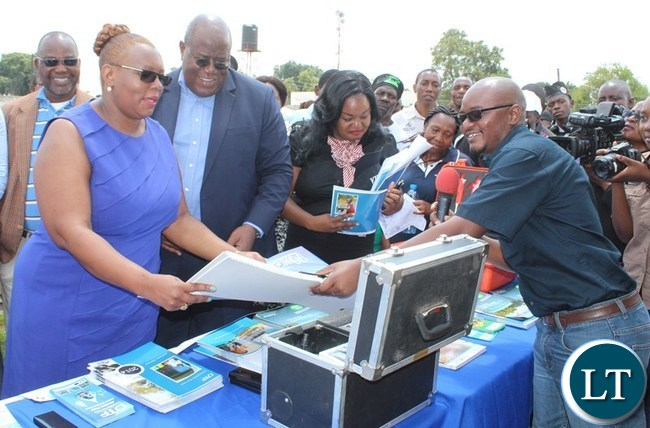 ENERGY and Water Development Minister Dora Siliya receives some paper materials from National Water Supply and Sanitation Council (NWASCO) Technical Inspector Curtis Muleya. This was during the Water day celebration at Choma Independence stadium
