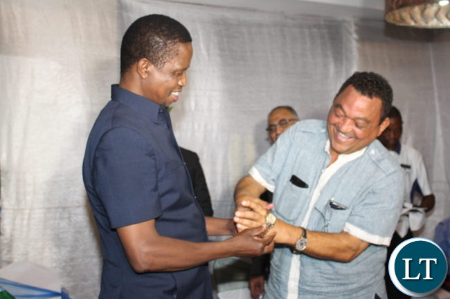 PRESIDENT Edgar Lungu puts a Rolex wrist watch on Valden Findlay's wrist after he pledged to but it at Fifty thousand Kwacha during a fundraising dinners for the ruling Patriotic Front held at Protea Hotel