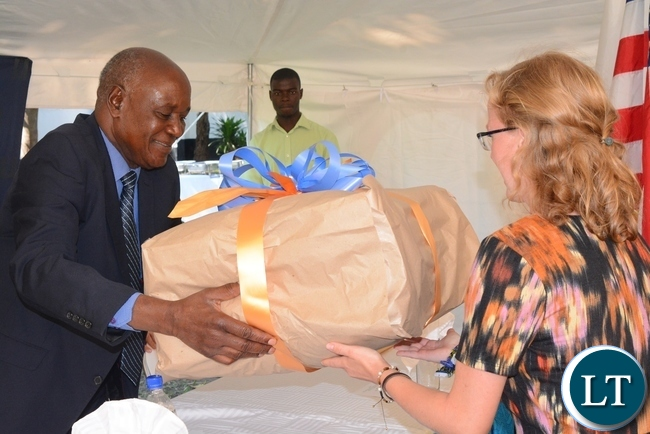 Busoli royal establishment Principal adviser John Luputa(l) being presented with a gift by one of the peace corps volunteers Kelsi Grogan(r) during the swearing in ceremony for rural aquaculture promotion and linking income,food and environment project volunteers