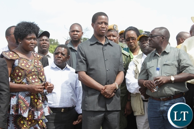 President Edgar Lungu (c) listens from Pettit and Partners Consultants Resident Engineer Ernest Masaiti (r) the contractors of Sioma Bridge as Road Development Agency (RDA) Communications Director Loyce Saili (l) looks on during the official commissioning of the bridge built at a cost of K108.2million in Sioma District of Western Province