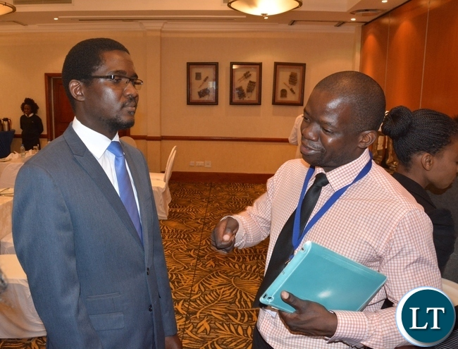 Inspector-Pensions and Insurance Authority Chishiba Kabungo chats with Director Consumer Protection Brian Lingela at the Press Briefing on fraud Prevention Month Media Breakfast at Southern Sun