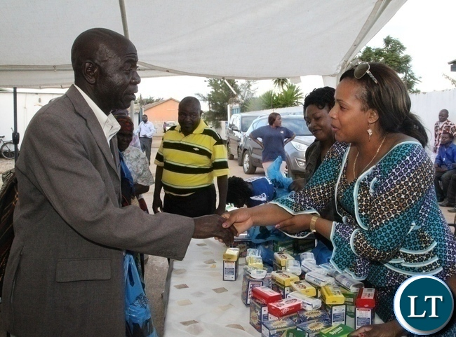 One of the beneficiaries of Divine Mercy Home Care Baidwin Chungu(l) thanking wife to kabwata area member of parliament Ireen Lubinda(r) for donating assorted goods to the aged in Chilenje