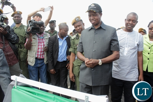 President Edgar Lungu (c) reads the message on the plaque after officially commissioning the Sioma Bridge built at a cost of K108.2million in Sioma District of Western Province,