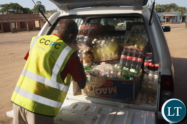 Southern Province CCPC Investigator, Chipapa Matyola loading seized expired drinks from some shop at Sinazeze Market in Sinazongwe District.- Picture by Hanford Chaaba.)