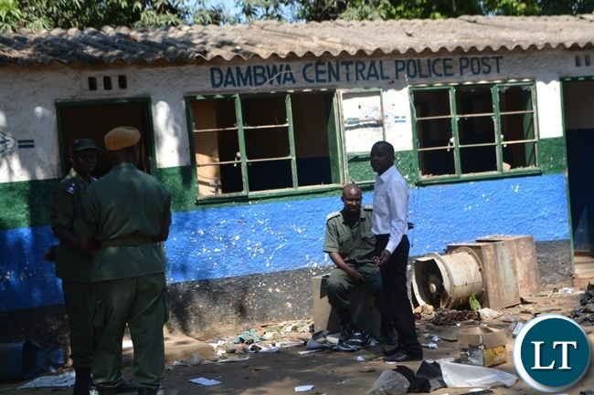 Police officer guarding remains of Dambwa Central Police Post which was attacked and damaged by irate Livingstone residents