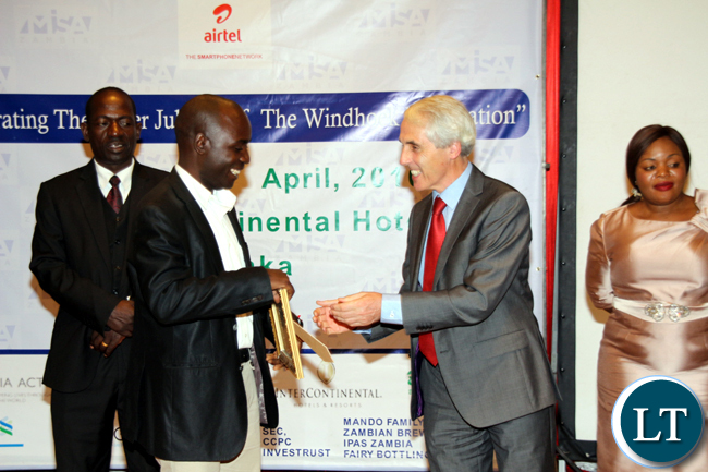 Darlington Mwendabai of Zambia Daily Mail receives an award for best tourism and hospitality reporting during the 2016 MISA Zambia annual awards in Lusaka on April 29, 2016.