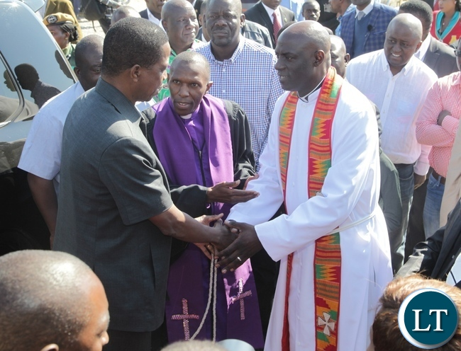 President Edgar Lungu being welcomed at Kabundi Kapisha UCZ Congregation Bishop Sichilima (c) and Rev. Alinjavwa Simumba shortly before Church services