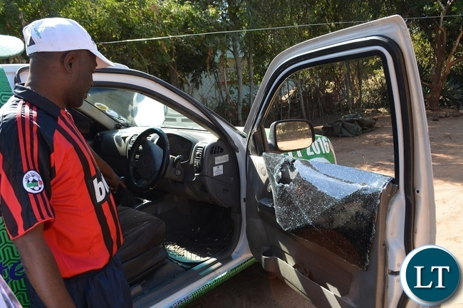 PF Livingstone vice district information and publicity secretary Philemon Musonda (in black and red t-shirt) showing the extent of the damage to the vehicle that was attacked by suspected UPND cadres in Zambezi ward Livingstone