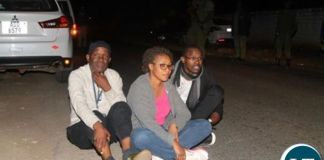Fred Mmembe with wife Mutinta and Joseph Mwenda sit outside Bwinjimfumu road after they were arrested