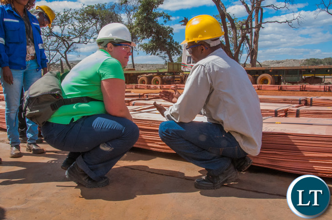 Head of the Office of the High Commission of Canada in Lusaka Amy Galigan inspects copper at First Quantum Minerals' Kansanshi mine.