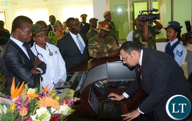 Sycom Africa Business Development Manager Mina Karas(r) shows President Lungu(l) the Digital login system for Patients at the reception at the State of the Art Zambia Air Force Hospital
