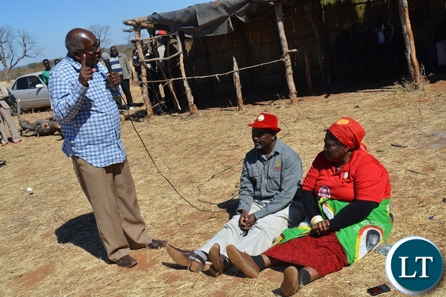 Former Southern Province Minister Daniel Munkombwe(holding microphone) counsels UPND Livingstone parliamentary candidate Mathews Jere(left in red hat) during a rally to drum up support for UPND Presidential,parliamentary and local Government candidates atMahululu clinic in Livingstone