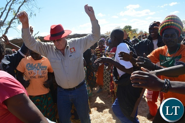 Chisekesi farmer and businessman Michael Couvaras dancing with UPND supporters during a rally to drum up support for UPND Presidential,parliamentary and local Government candidates atMahululu clinic in Livingstone