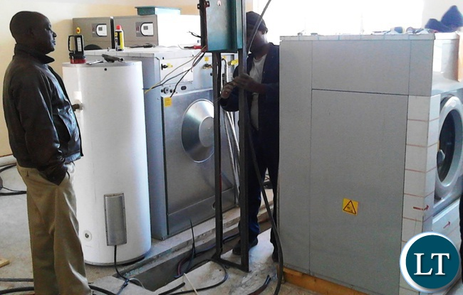 Electricians from the Ministry of Health installing washing machines at the laundry room at the newly constructed Serenje district hospital in readiness for the commissioning of the hospital.