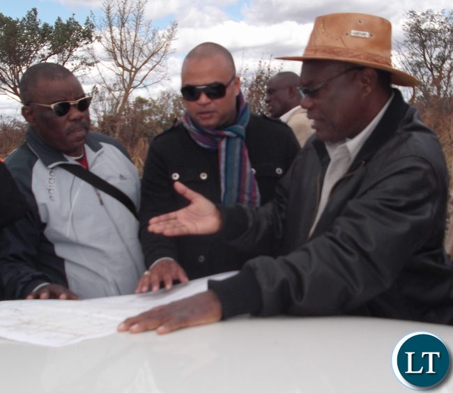 Luapula Province Minister Brigadier General Benson Kapaya showing the 600 mega Watts Solar energy production farm investors Brylan Koko (Middle) and Agrippa Xulu of Devine Solutions from Derban South Africa who are in the Country with plans to invest in solar energy production in Chembe District. Here the Minister is showing them the Map with a specific preferred location of where the Farm should be located.