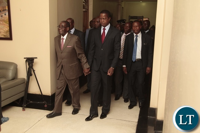 President Edgar Lungu walks hand in hand with President Robert Mugabe of Zimbabwe at State House