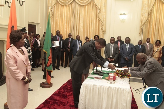 President Edgar Lungu flanked by Vice President Inonge receive latter of Oath from Newly appointed Minister of General Education Dennis Wachinga taking Oath before and during swearing in ceremony at State House