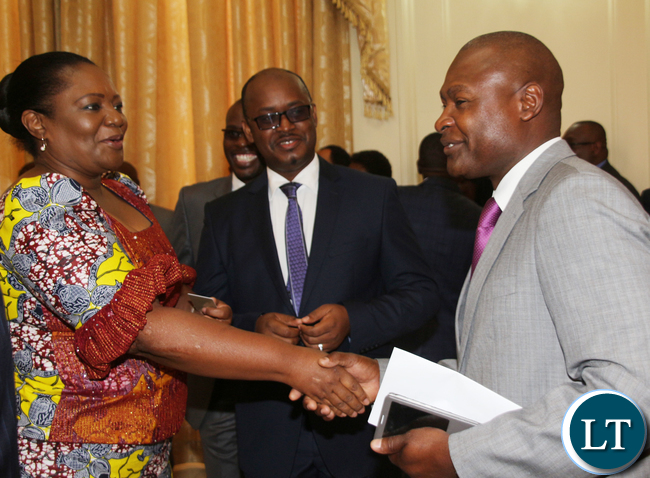 PF Deputy Spokesperson Fr Frank Bwalya congratulating State House PS Christah Kalulu while looking on PF Media Committee member Sunday Chanda.