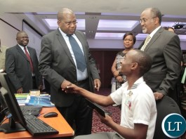 Health Minister Chitalu Chilufya chats with E-learning student nurse of Kitwe Mwaba Zulu whilst Child fund Reginal Director Victor Koyi (l) and Child fund Zambia National Director Dereje Adugna (r) looks on during the launch of the roll out of E-learning as a training Methodology in Zambia