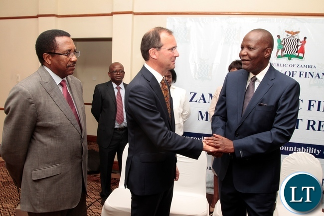Minister of Finance Felix Mutate shake hands with British High Commissioner to Zambia Fergus Cochrane after signing ceremony of the first amendment to the grant agreement of the Public Financial Management Reform and launch of the Zambia PEFA assessment 2016 whilst Secretary to the Treasury Fredson Yamba